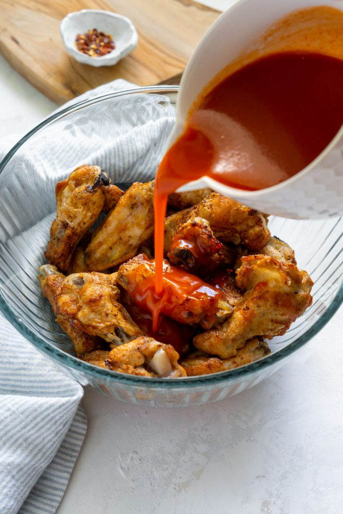 pouring buffalo sauce over wings in a glass bowl