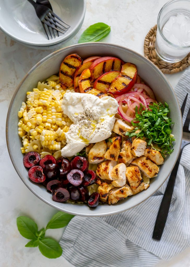 corn, burrata, grilled peaches, chicken, cherries, and red onions in a large bowl and a glass of water