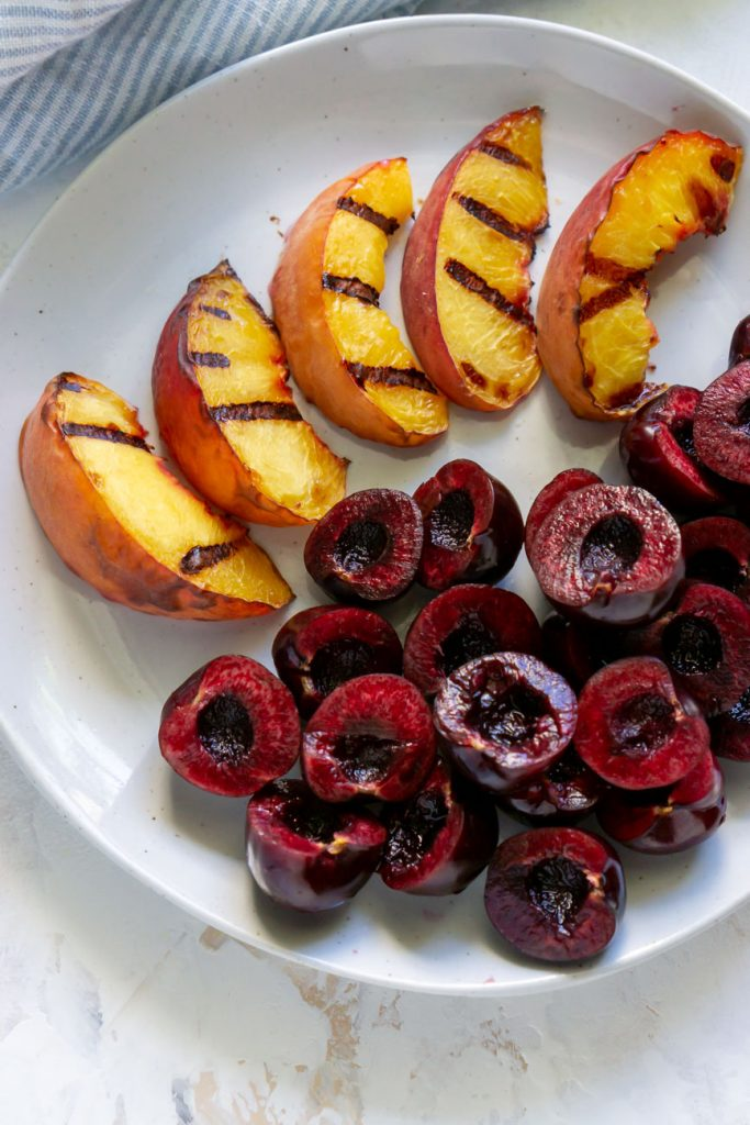 grilled peaches and cherries on a plate