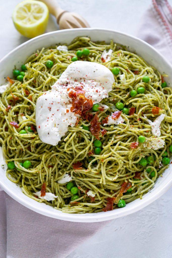 mint pesto prosciutto pasta in a large white bowl with burrata