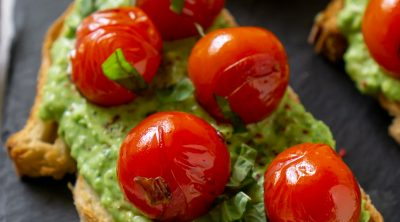pea pesto tomato crostini on a black slate