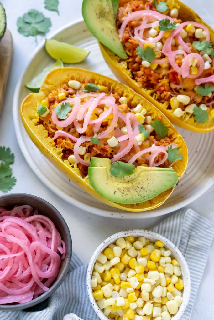two taco spaghetti squash boats on a white plate with lime wedges