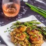 scallops over mushroom risotto on a white plate with asparagus