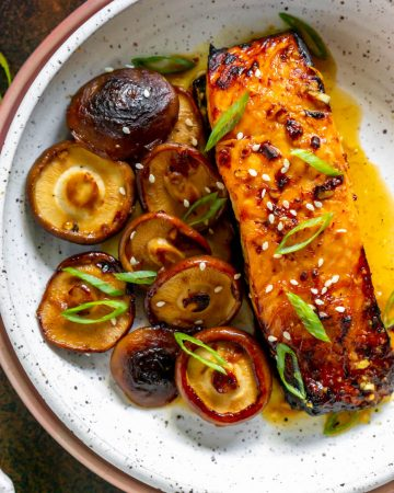 asian salmon with mushrooms in a white bowl