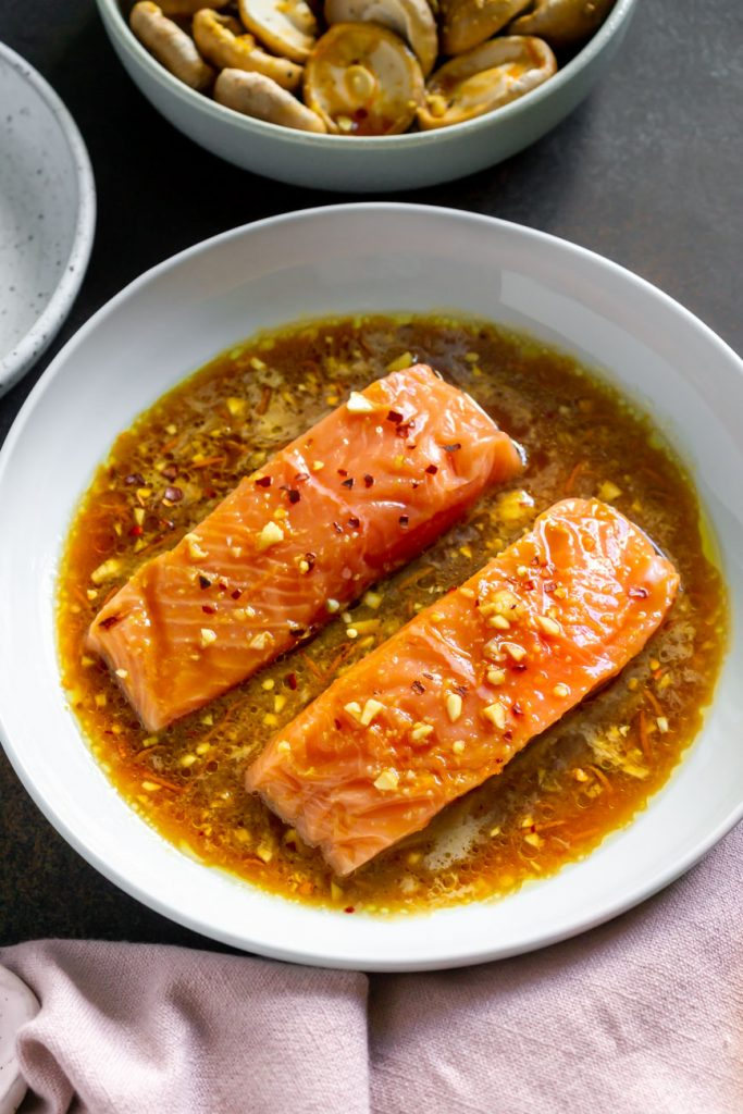 two salmon fillets marinating in a white bowl