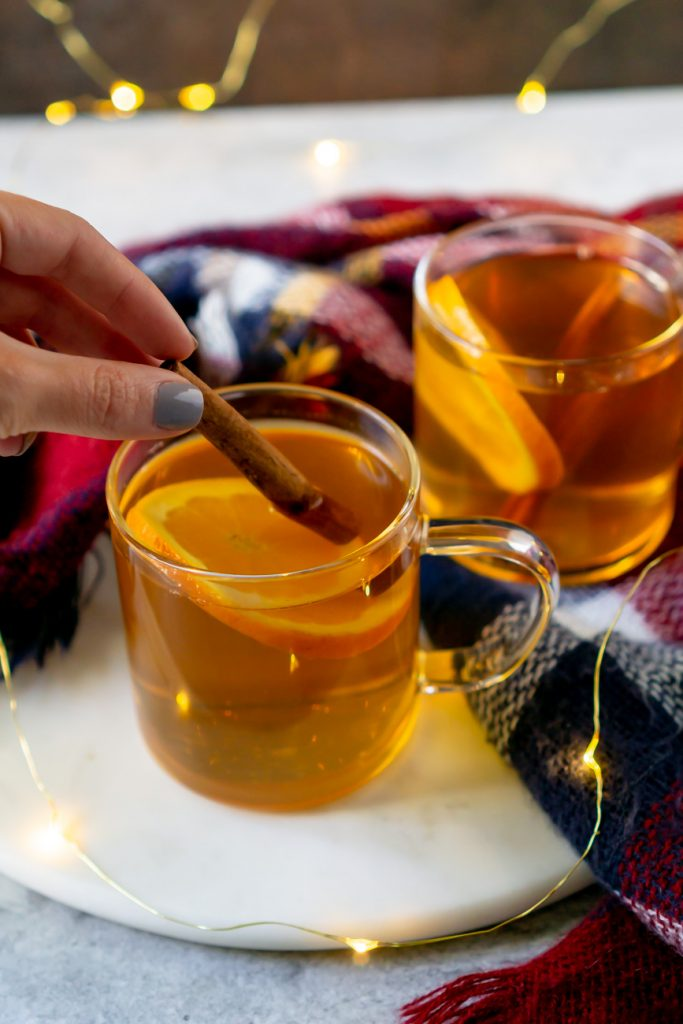 garnishing a hot toddy with a cinnamon stick