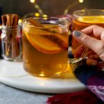 hot toddy in a glass mug with cinnamon sticks