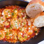 shrimp saganaki in a black bowl with bread