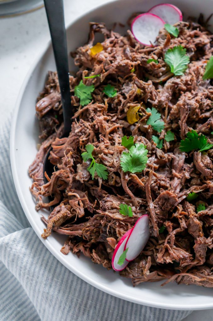chipotle barbacoa in a white bowl with a black spoon