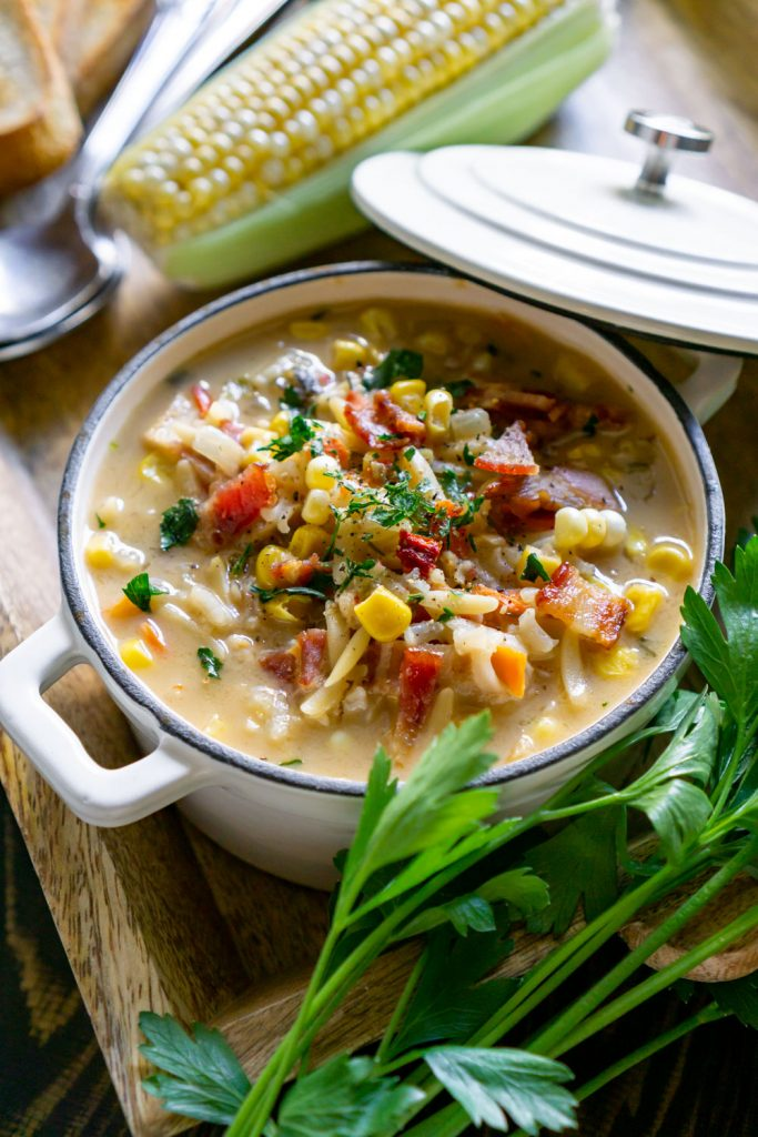 corn chowder in a white bowl with parsley