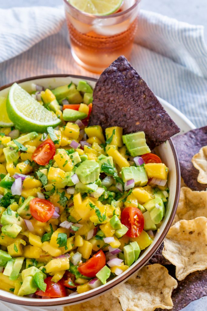 mango salsa in a bowl with chips and lime wedges