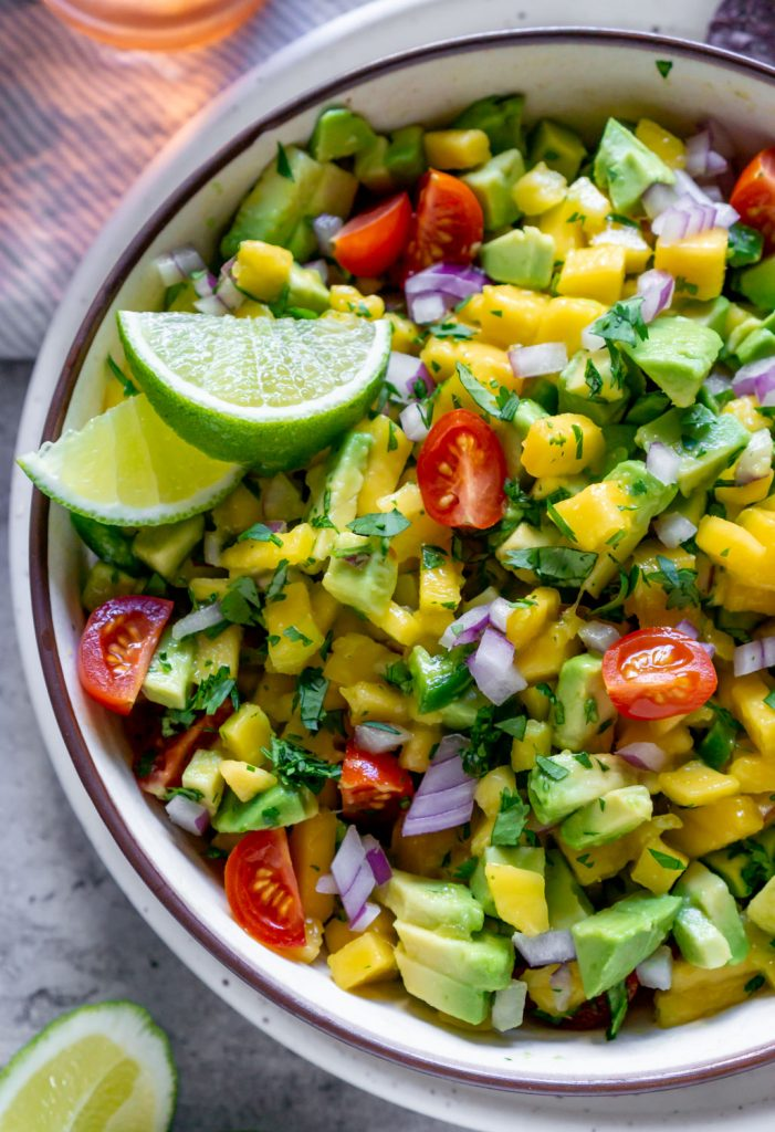 mango salsa in a bowl with lime wedges