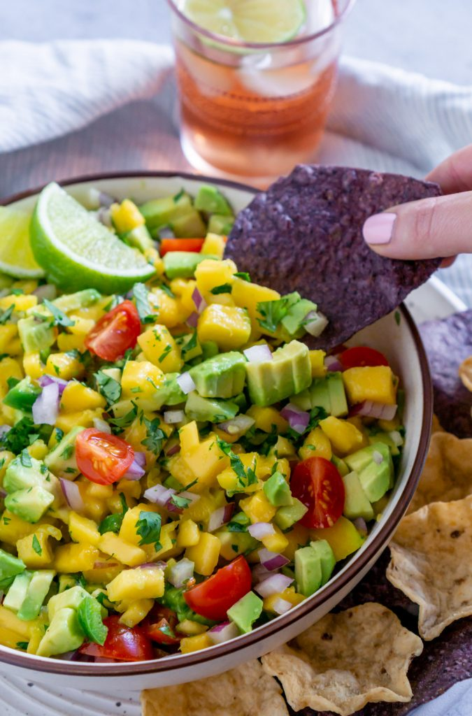 dipping a chip in mango salsa