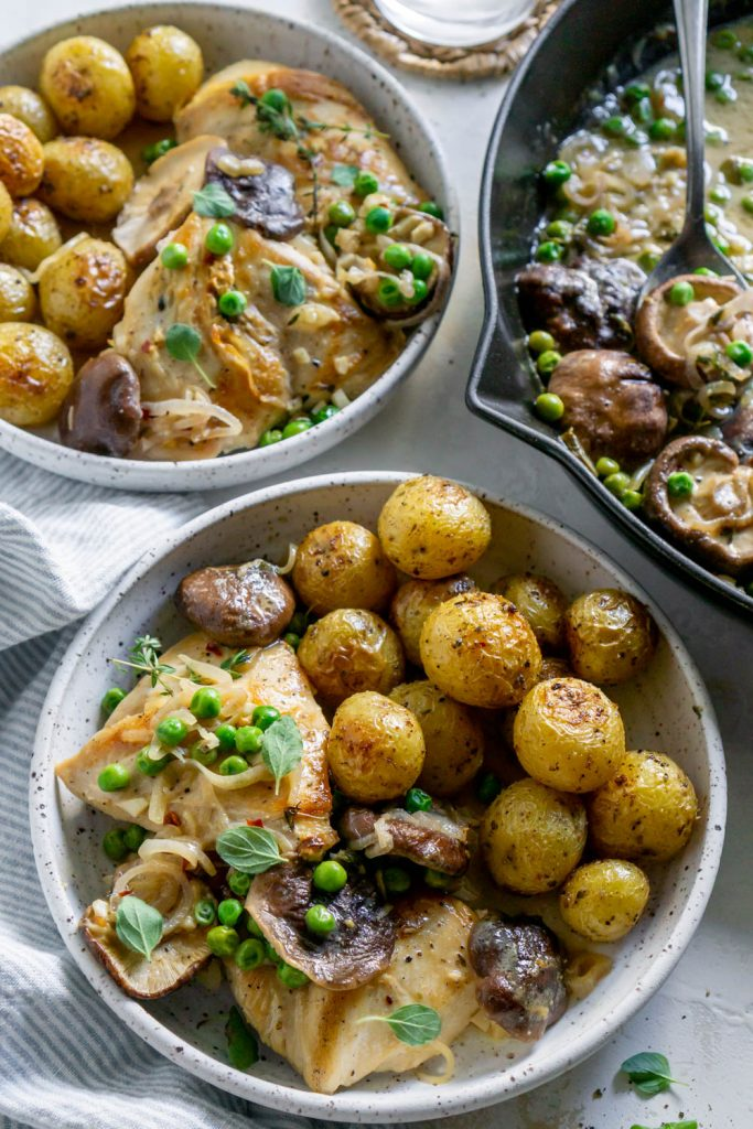 skillet chicken with potatoes in two white bowls