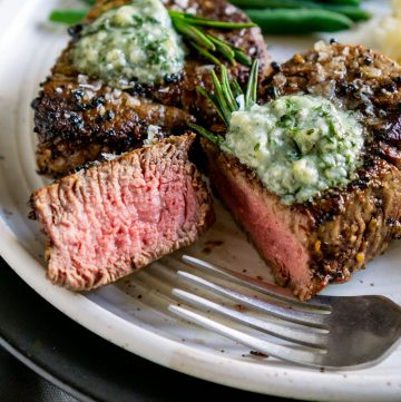 sliced filet mignon on a plate with a fork and green beans