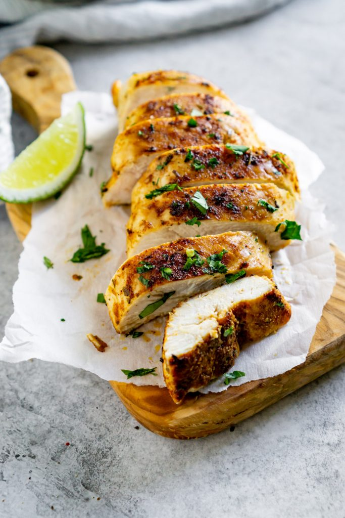 sliced chicken on a wood serving board