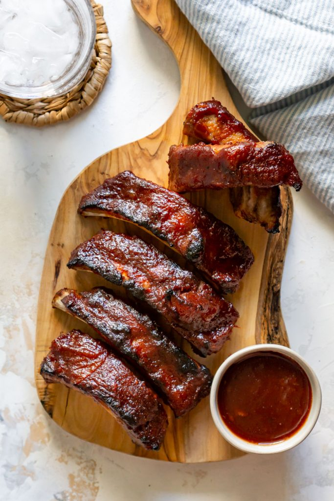 slow cooker ribs, glass of water, and bbq sauce