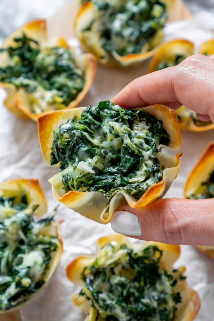hand holding a spinach and artichoke dip wonton cup