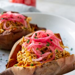bbq chicken stuffed sweet potato on a white plate