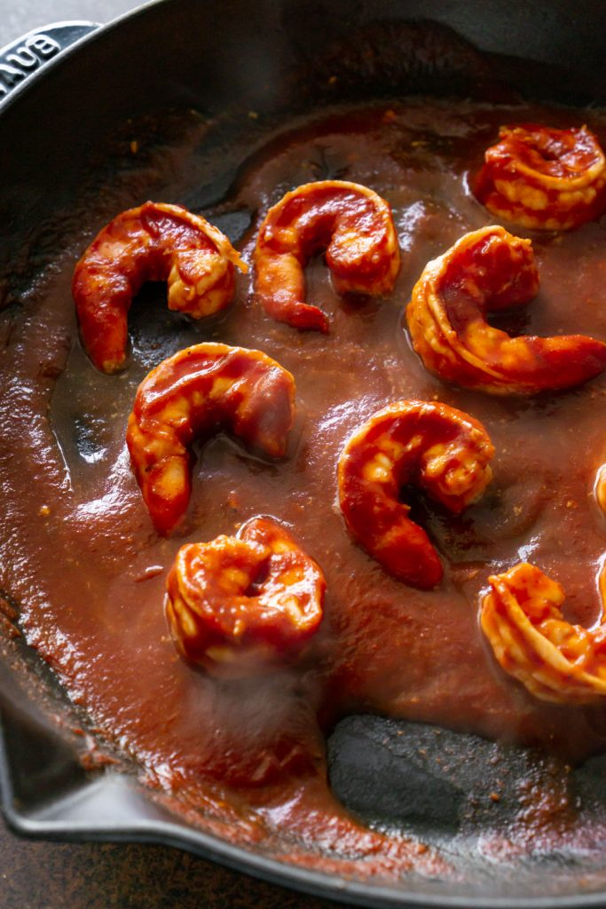 cooking shrimp in a pan with bbq sauce
