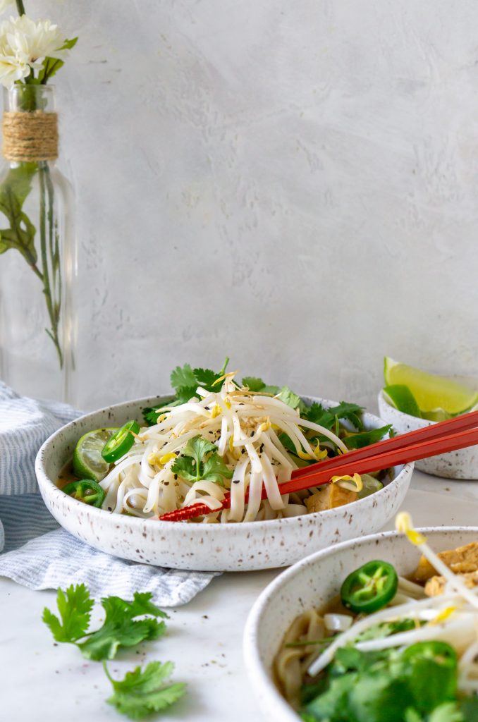 two bowls of chicken pho with chopsticks