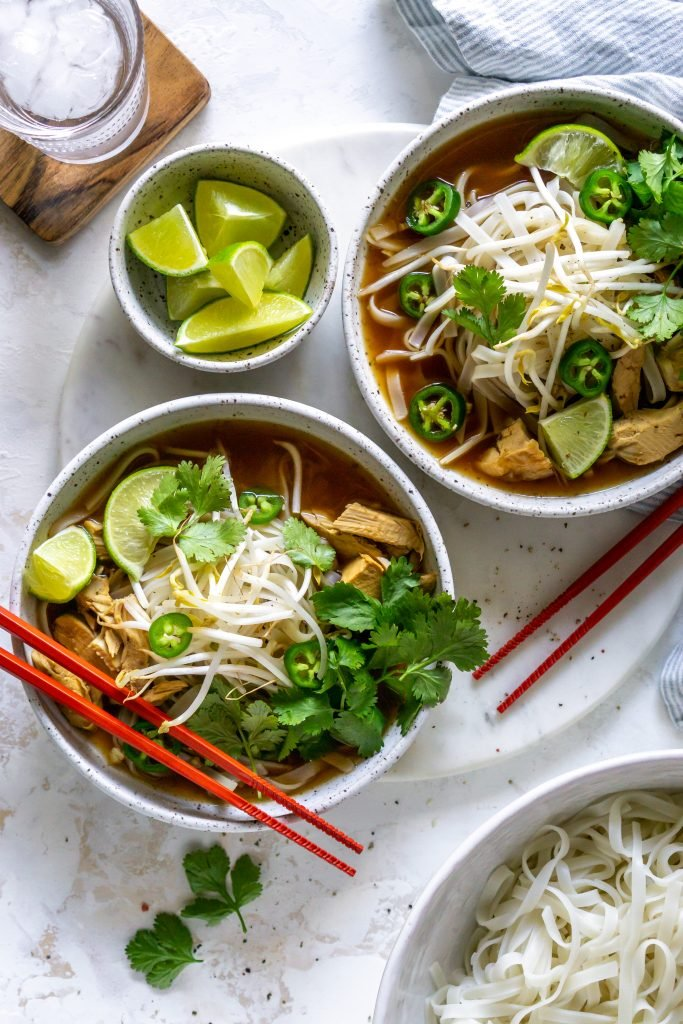 two bowls of pho, glass of water, and bowl of limes