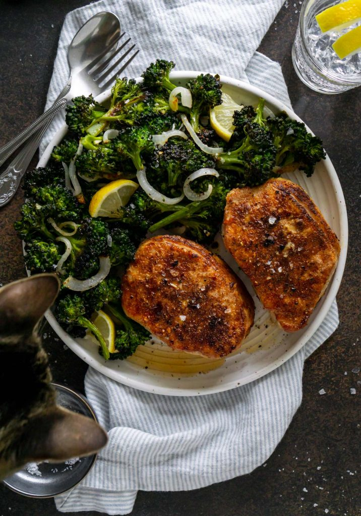 two pork chops on a plate with broccolini and a cat peeking over the plate