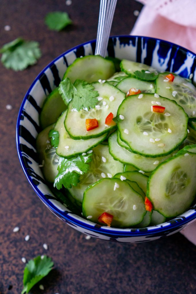 asian cucumber salad in a blue bowl with a pink napkin and cilantro