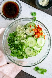 cucumbers, chili peppers, cilantro, and sesame seeds in a glass bowl