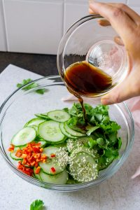 pouring dressing onto cucumber salad