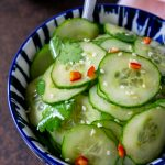 asian cucumber salad in a blue bowl