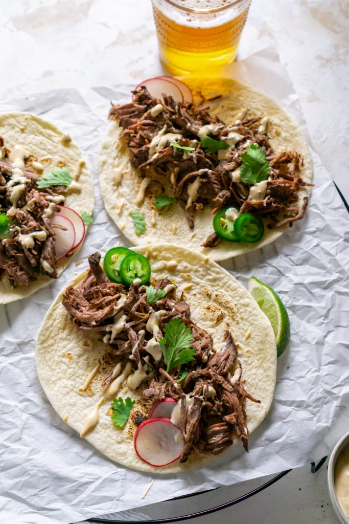 three barbacoa tacos with beer