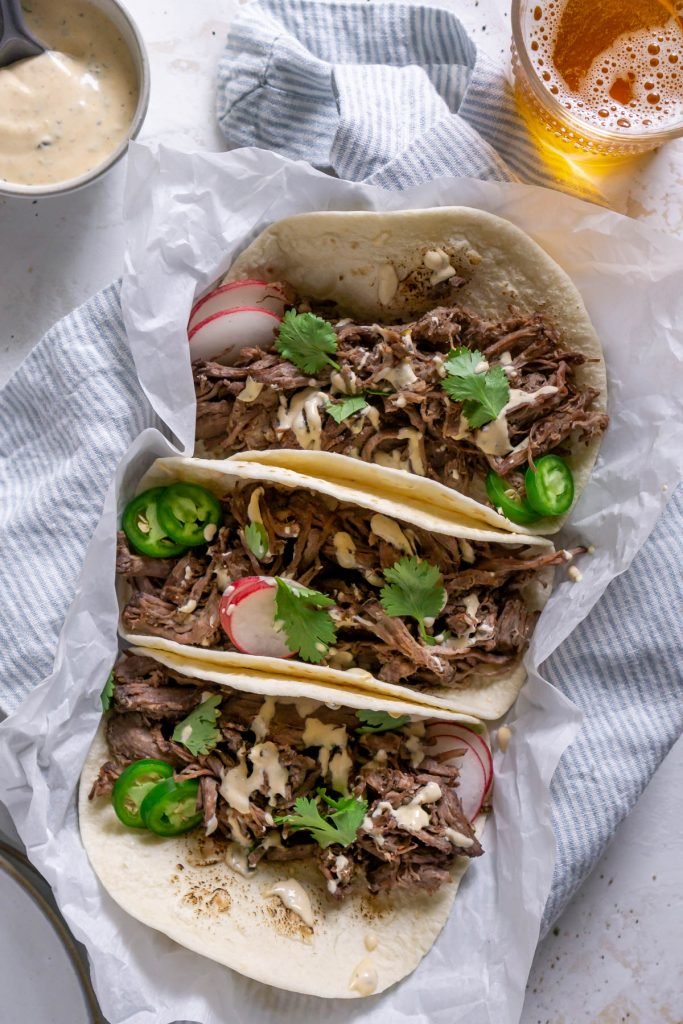 barbacoa tacos with a blue napkin and crema