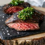 chimichurri steak on a black slate board