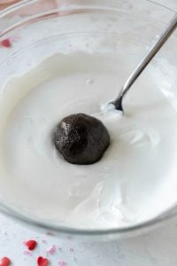dipping oreo ball into white melted candy