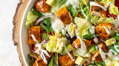 crispy buffalo chicken salad in a large white bowl with buffalo sauce on the side