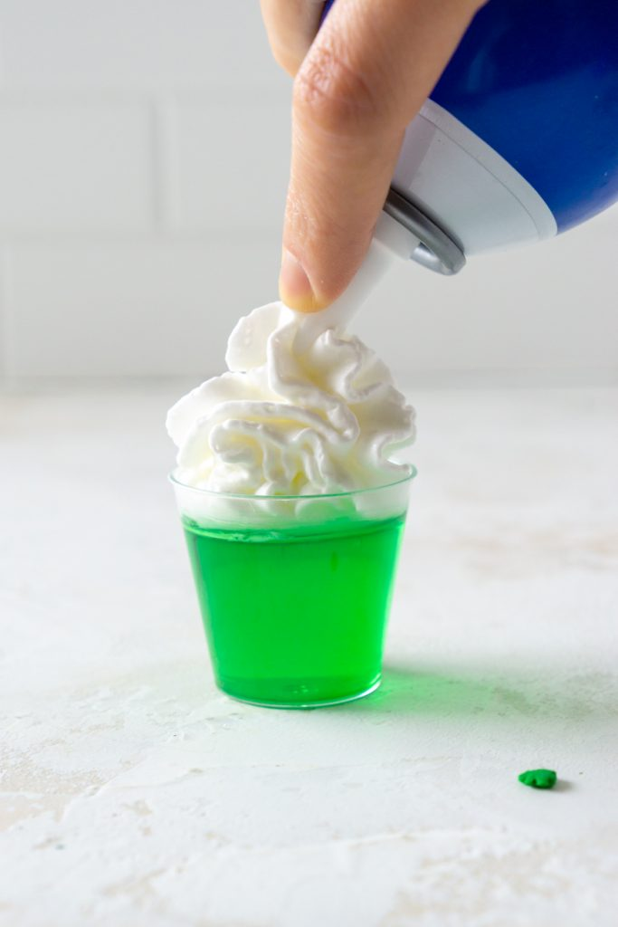 putting whipped cream on top of a green jello shot