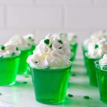 green vodka jello shots on a marble serving tray
