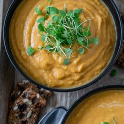 roasted butternut squash soup in a black bowl with micro greens