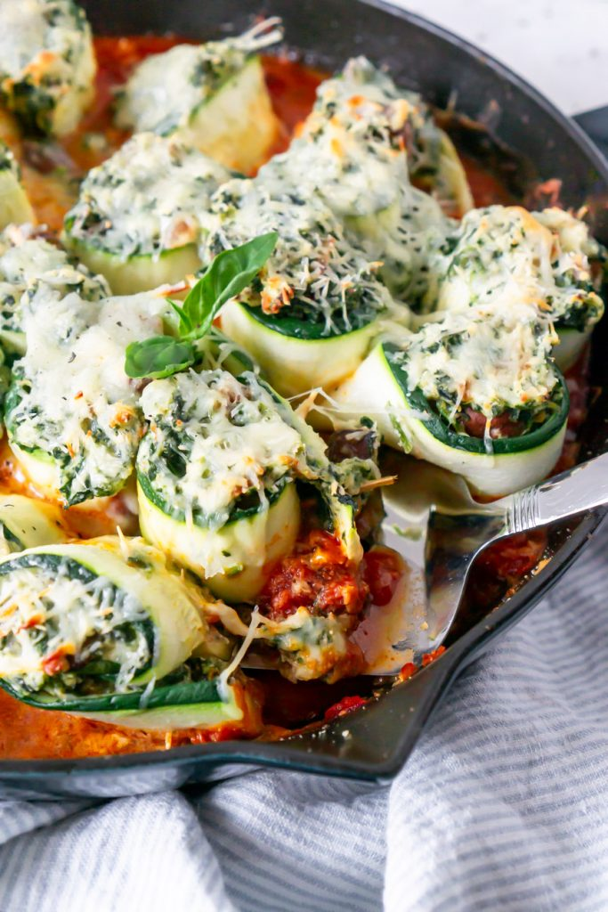 zucchini lasagna rolls in a skillet with a spatula