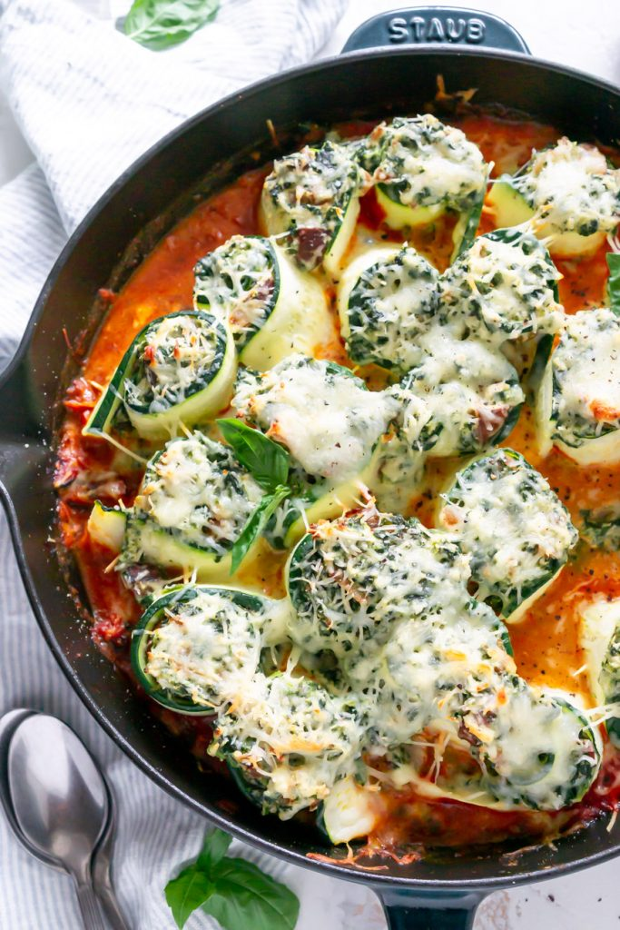 zucchini lasagna rolls in a skillet with a silver spoon