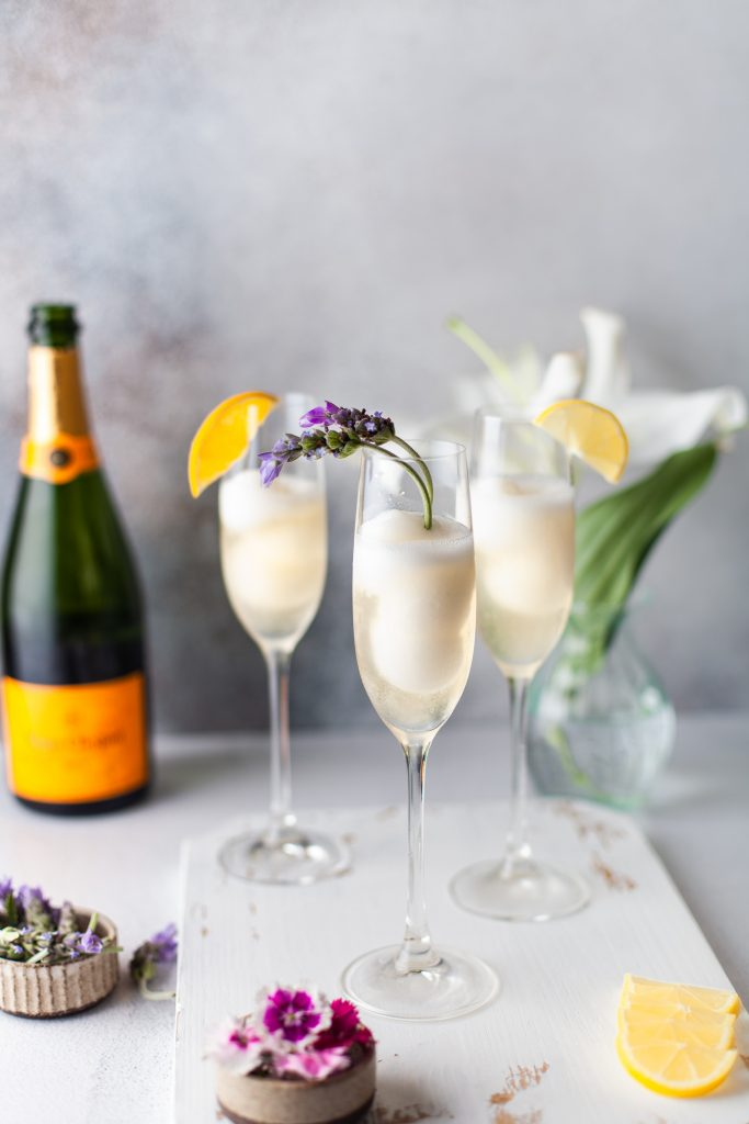 3 champagne cocktails on a wood serving board with flowers