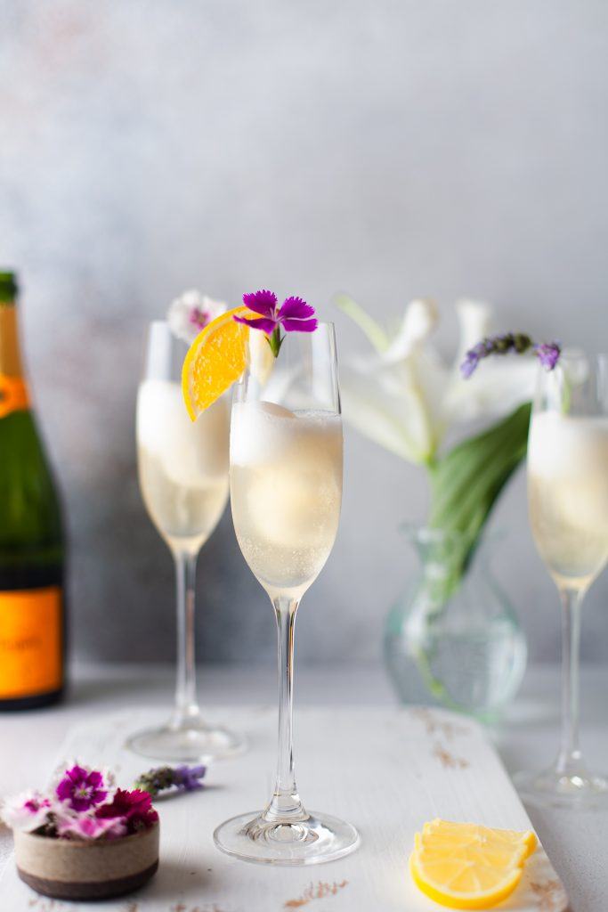 2 champagne cocktails on a white serving tray