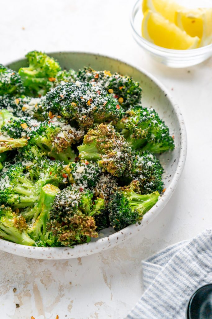 air fryer broccoli in a white bowl and lemon wedges