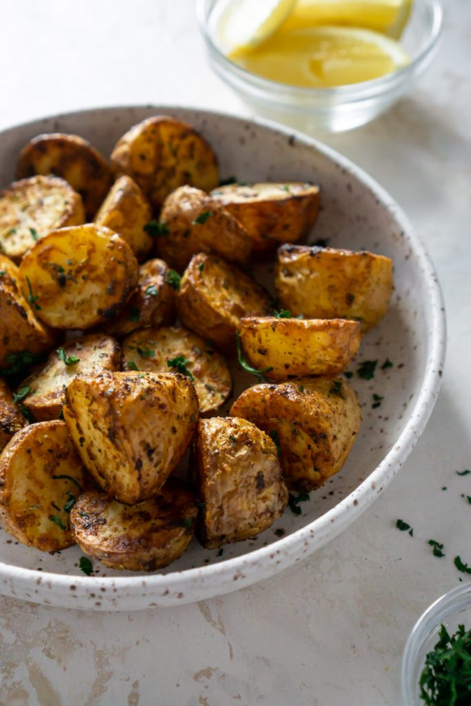 air fryer potatoes in a white bowl with lemons
