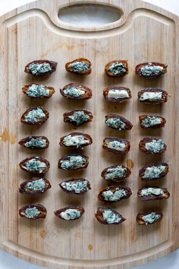 blue cheese stuffed dates on a cutting board