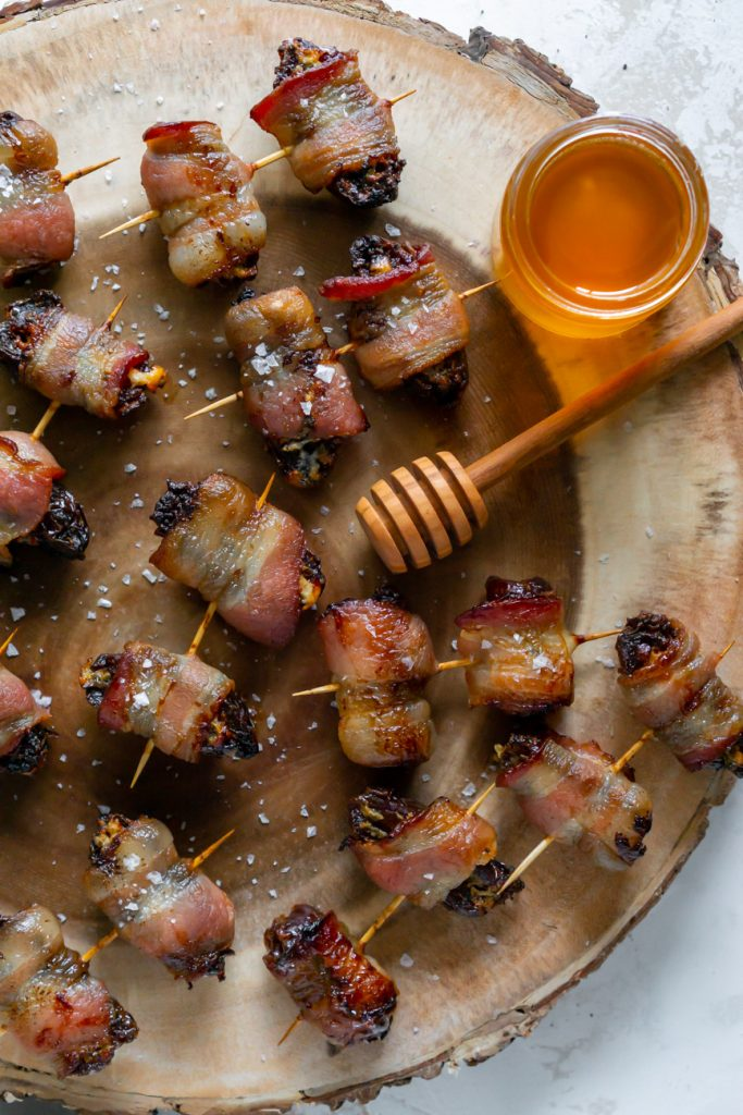bacon wrapped dates on a wood serving tray with honey