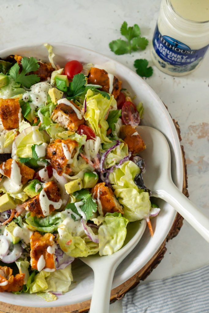 salad in a bowl with tongs and dressing on the side