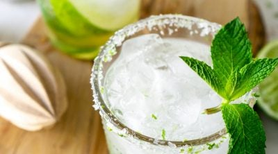 two mint mojitos on a wood serving tray