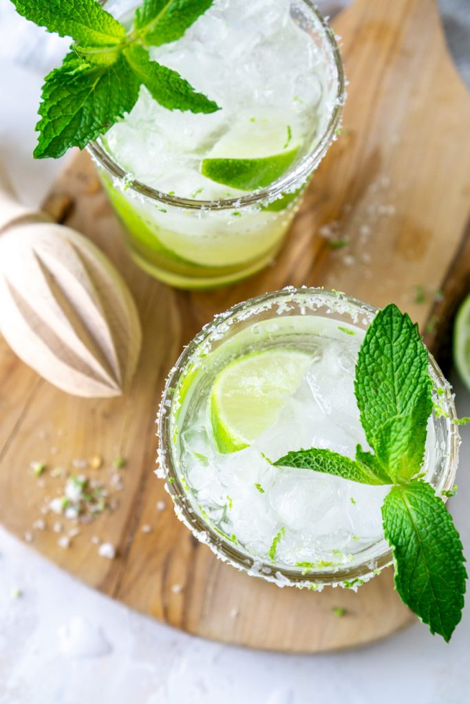two mojitos with fresh mint and a wooden juicer
